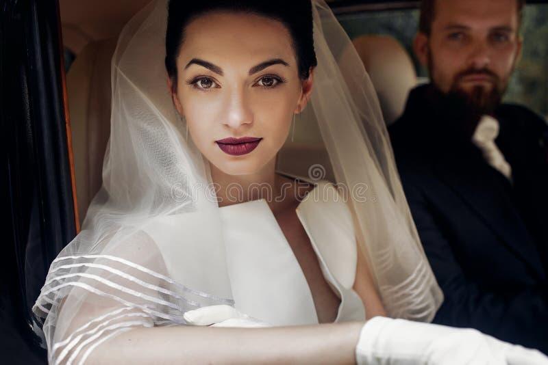 Het paar van het luxe het elegante huwelijk stellen in modieuze zwarte auto kloof stock foto