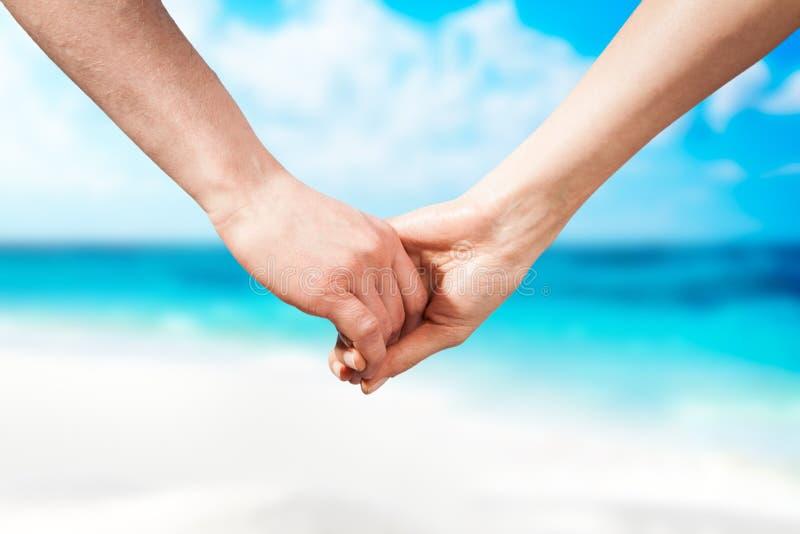 Het paar van holdingshanden op strand royalty-vrije stock afbeeldingen