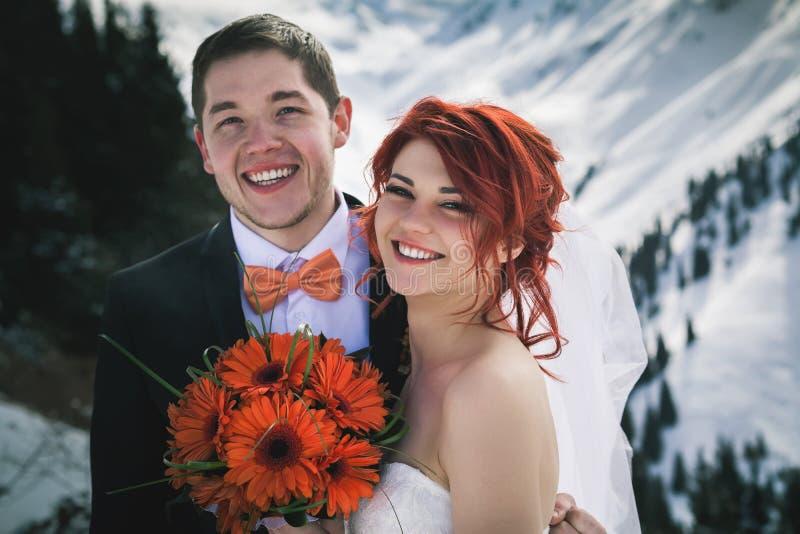 Het paar van huwelijkssnowboarders bij de bergwinter die enkel wordt gehuwd stock afbeelding