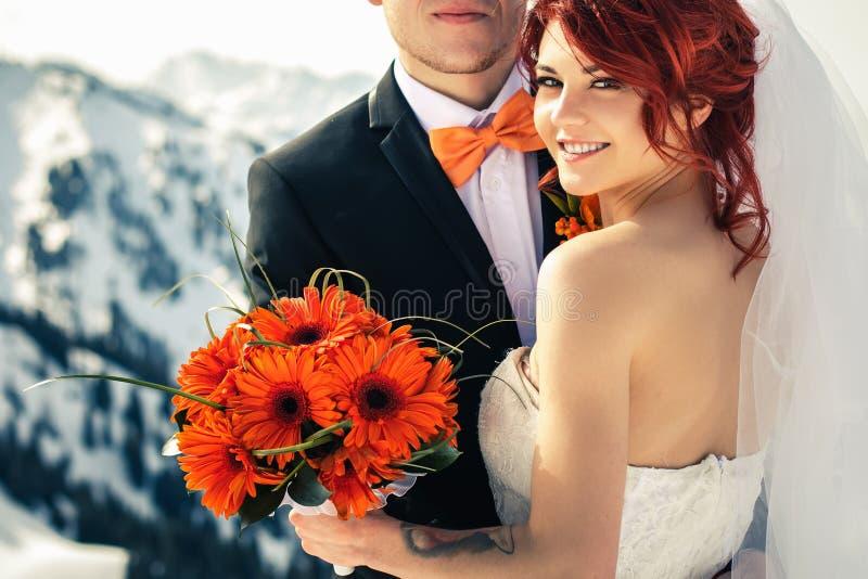 Het paar van huwelijkssnowboarders bij de bergwinter die enkel wordt gehuwd stock foto's
