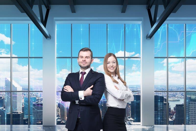Het paar van jonge managers bevindt zich in het moderne panoramische bureau De mening van New York De financiële grafieken worden stock afbeelding