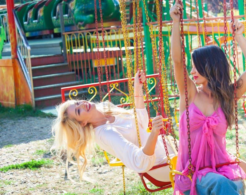 Het paar van jonge maniermeisjes heeft pret op vliegende carrousel in de pretparkzomer stock foto's