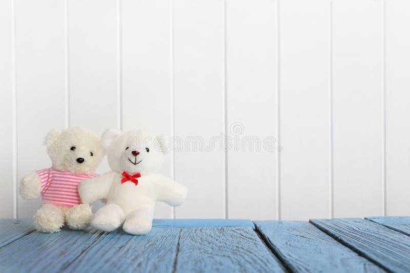 Het paar van klein wit draagt zittend op blauwe houten lijst aangaande witte houten muur stock foto's