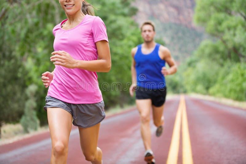 Het paar van marathon lopende atleten opleiding op weg stock afbeeldingen
