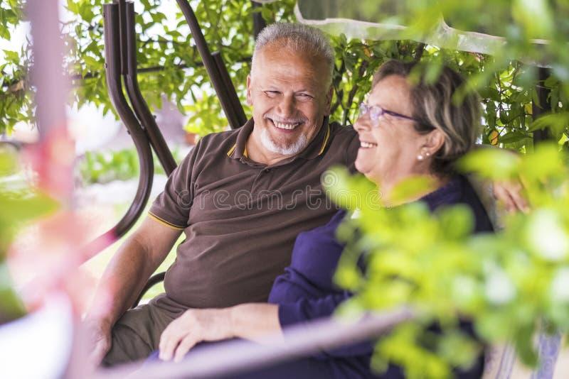 Het paar van Nice van mooie Kaukasische oude oudste 70 jaar zit openlucht thuis hebbend pret met glimlachen en lach Het gelukkige royalty-vrije stock afbeelding