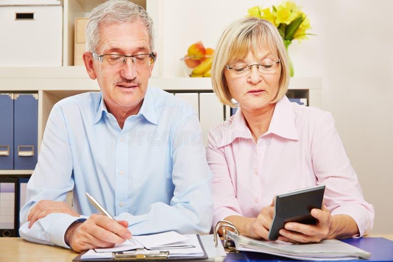 Het paar van oudsten maakt belastingaangifte stock foto's
