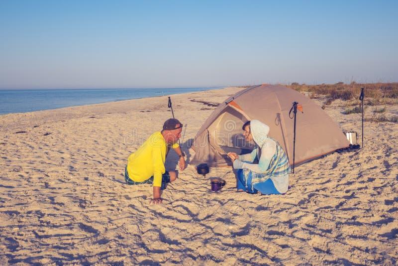Het paar van reizigers ontspant naast tent stock afbeeldingen
