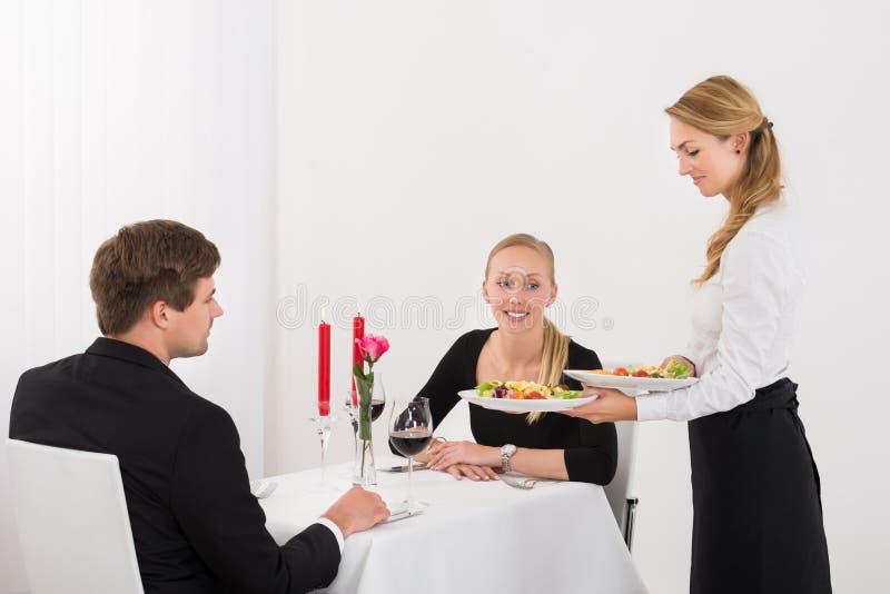 Het Paar van serveersterserving food to royalty-vrije stock foto's