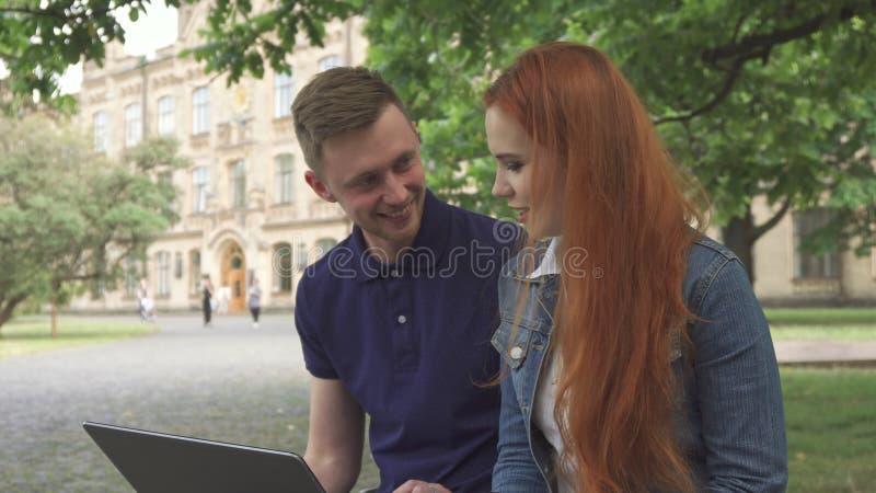 Het paar van studenten bespreekt iets op laptop op campus stock afbeeldingen