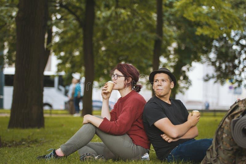 Het paar van tienerstoeristen met rugzakken die roomijs eten en heeft rust in het stadspark royalty-vrije stock foto's