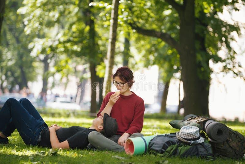 Het paar van tienerstoeristen met rugzakken heeft rust in het stadspark royalty-vrije stock foto's