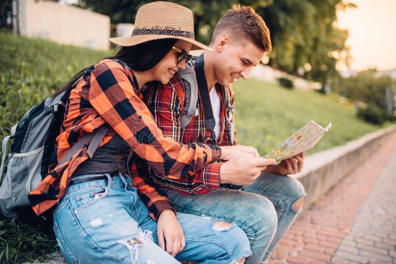 Het paar van toeristen bestudeert de kaart van aantrekkelijkheden royalty-vrije stock foto