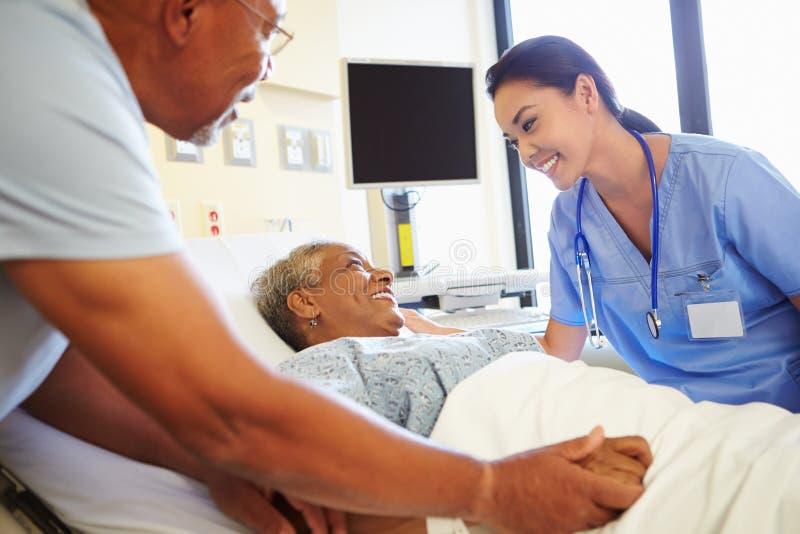 Het Paar van verpleegsterstalking to senior in het Ziekenhuiszaal stock foto