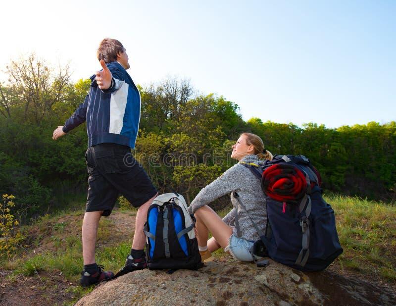 Het paar van Wandelaars met rugzakken die, kerel neemt een diepe adem rusten stock afbeelding