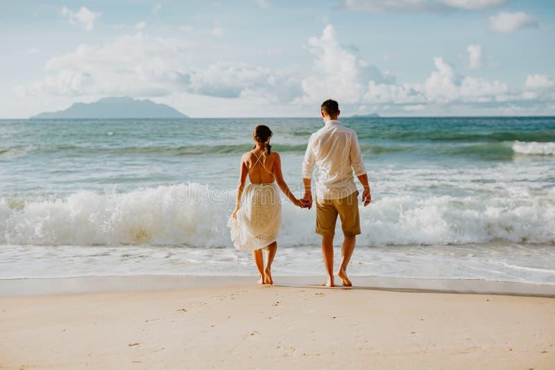 Het paar van het wittebroodswekenhuwelijk op strand bij zonsondergang stock fotografie