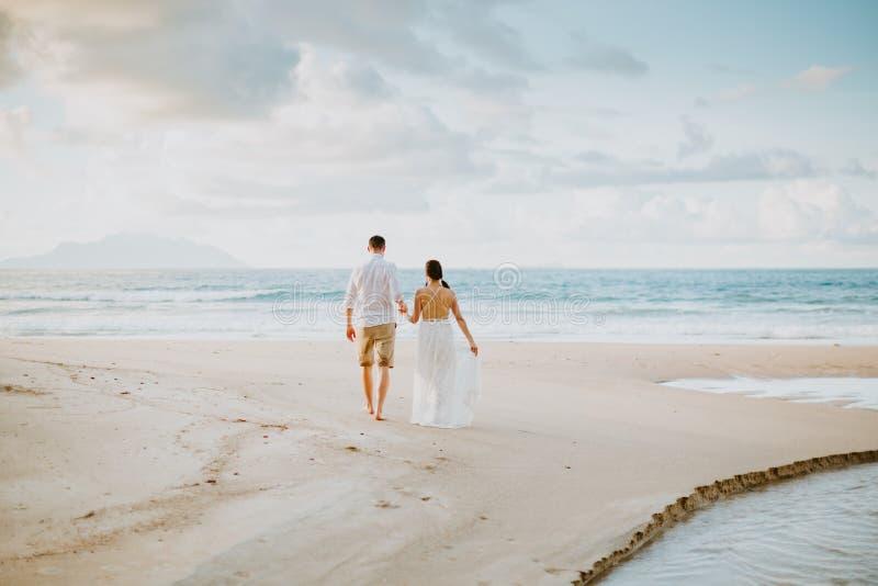 Het paar van het wittebroodswekenhuwelijk op strand bij zonsondergang stock foto's