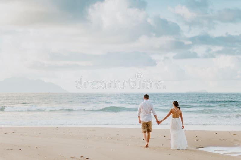 Het paar van het wittebroodswekenhuwelijk op strand bij zonsondergang stock foto