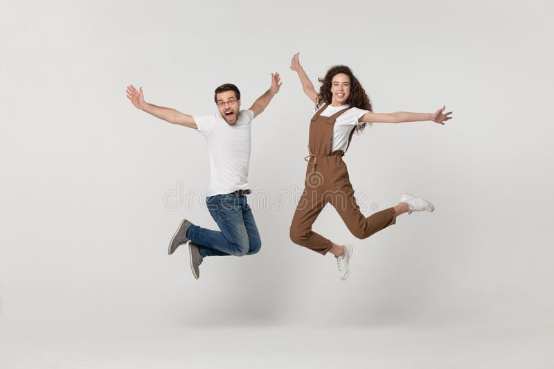 Het paar werd in een sprong gefotografeerd op grijze achtergrond wordt geïsoleerd die stock foto's