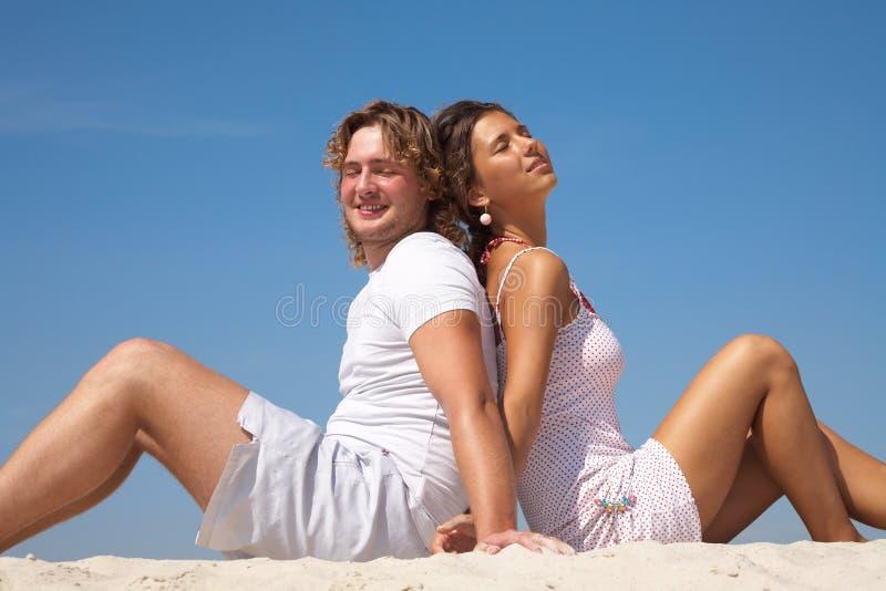 Het paar zit bij het strand royalty-vrije stock foto's