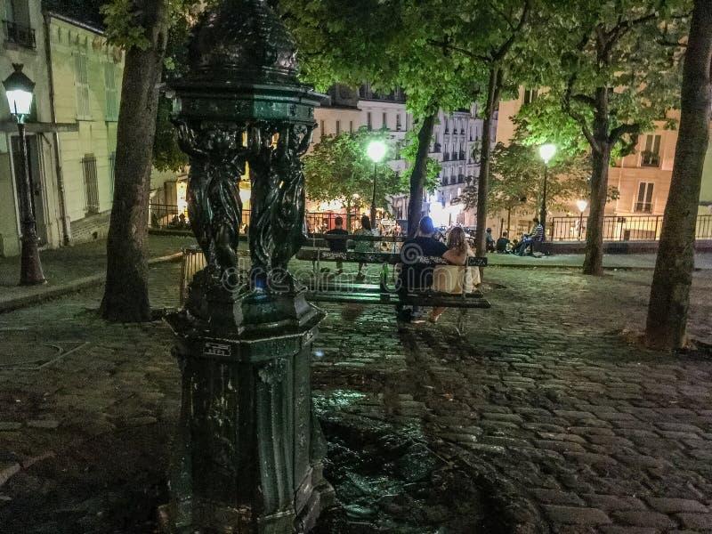 Het paar zit op bank in de avond van Parijs op Plaats Emile Goudeau op Montmartre royalty-vrije stock foto