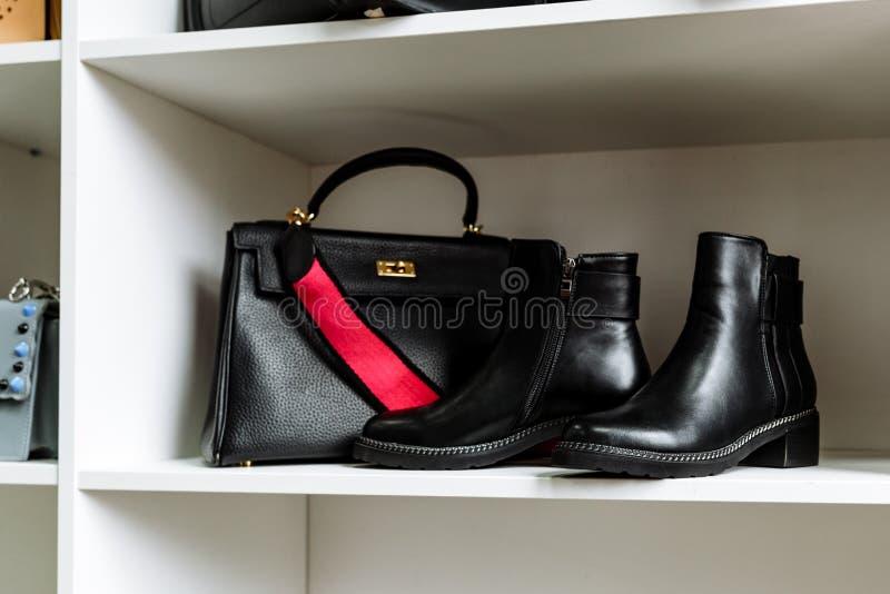 Het paar zwarte leerschoenen met lage hielen en een zwarte zak met een goud ontzetten en een rode riem op een witte plank in de o stock foto