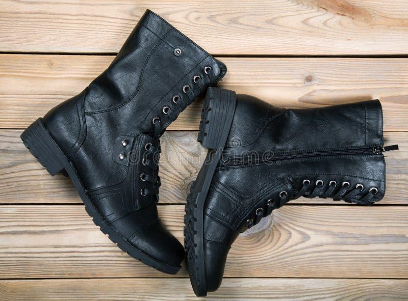 Het paar zwarte schoenen ligt op houten raad stock fotografie