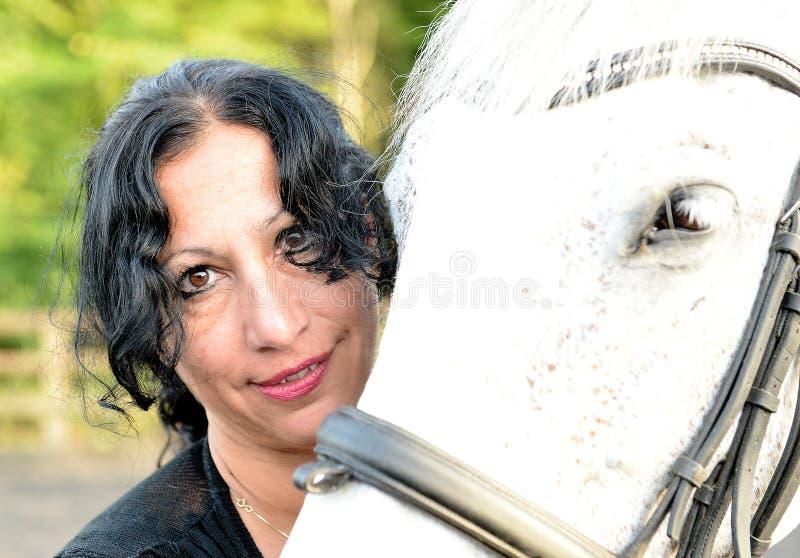 Het paard van de vrouwenholding stock foto's