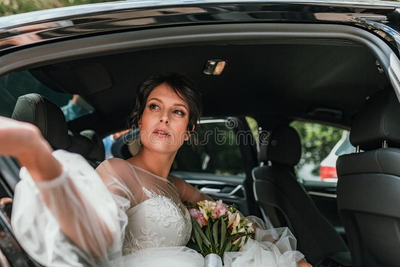 Het paarholding van het luxe dient de elegante huwelijk modieuze zwarte auto in schitterende bruid en knappe bruidegom in retro s stock foto's