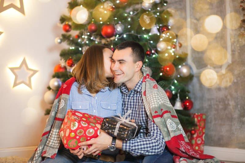 Het paarpaar in liefde onder een deken dichtbij de Kerstboom geeft elkaar giften royalty-vrije stock foto's