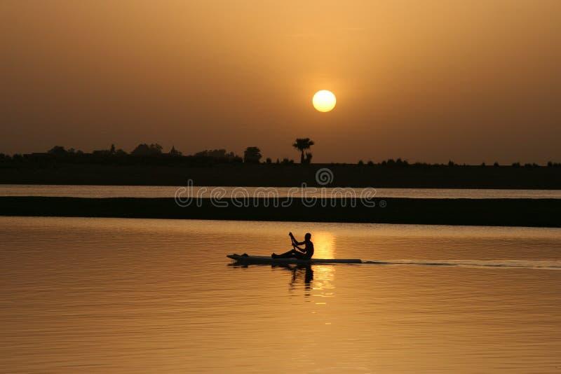 Het paddelen op het water bij zonsondergang stock foto's