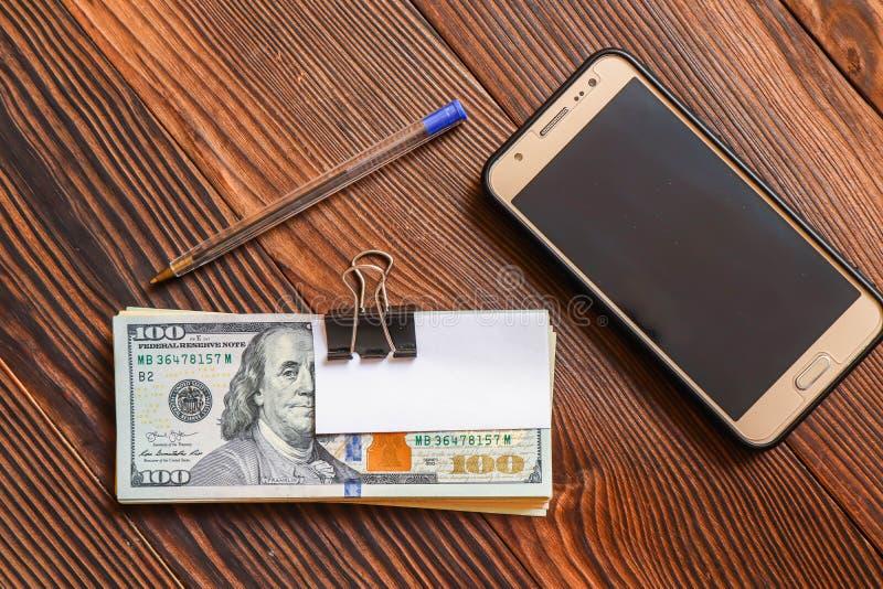 Het pak dollars telefoneert pen en document sticker voor uw tekst op houten achtergrond royalty-vrije stock afbeelding