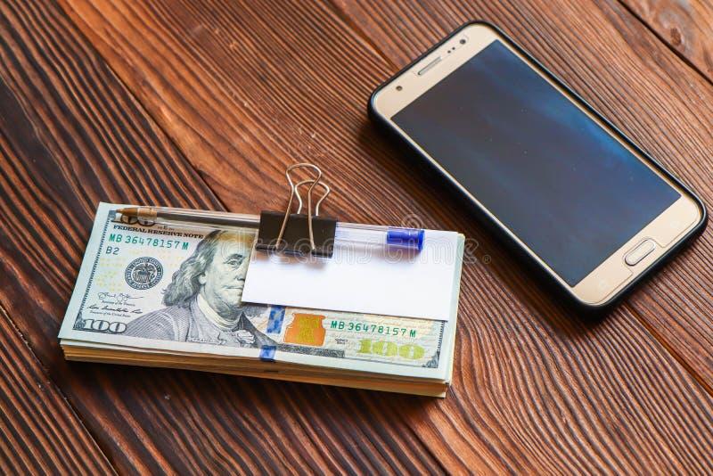 Het pak dollars telefoneert pen en document sticker voor uw tekst op houten achtergrond royalty-vrije stock foto