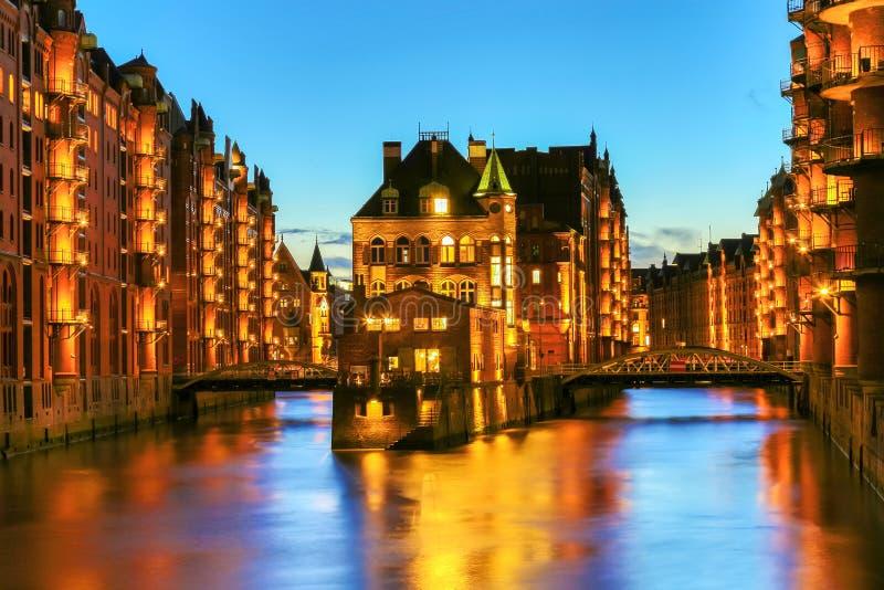 Het Pakhuisdistrict Speicherstadt tijdens schemeringzonsondergang in Hamburg, Duitsland Verlichte pakhuizen in Hafencity-kwart bi royalty-vrije stock fotografie