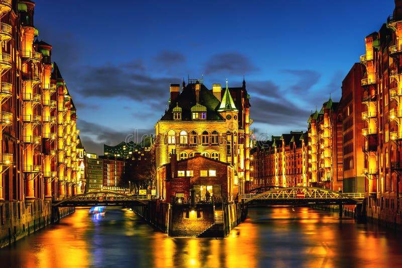 Het Pakhuisdistrict Speicherstadt tijdens schemeringzonsondergang in Hamburg, Duitsland Verlichte pakhuizen in Hafencity-kwart bi royalty-vrije stock afbeeldingen