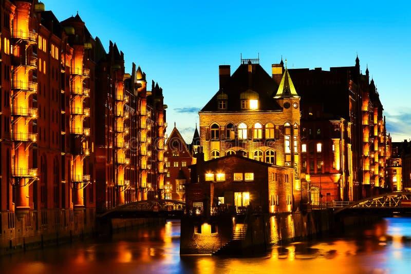 Het Pakhuisdistrict Speicherstadt tijdens schemeringzonsondergang in Hamburg, Duitsland Verlichte pakhuizen in Hafencity-kwart bi royalty-vrije stock foto