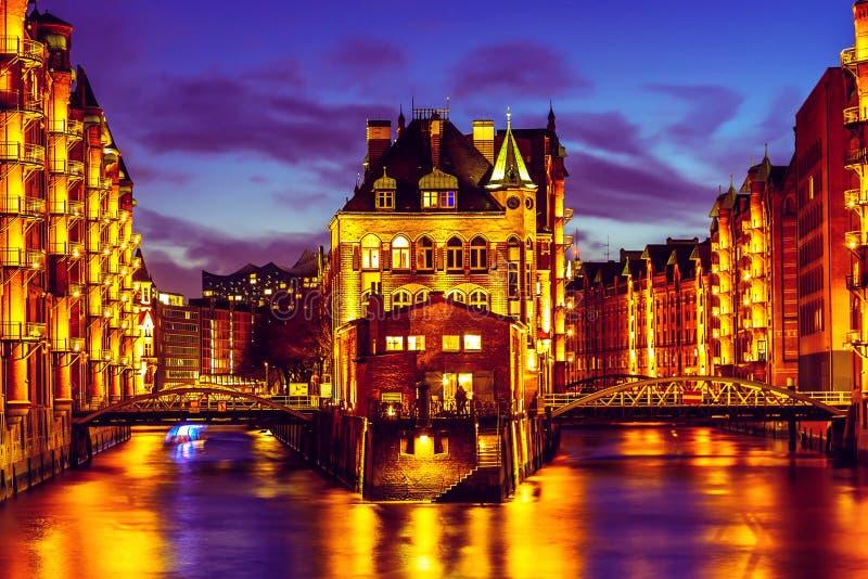 Het Pakhuisdistrict Speicherstadt tijdens schemeringzonsondergang in Hamburg, Duitsland Verlichte pakhuizen in Hafencity-kwart bi stock afbeeldingen