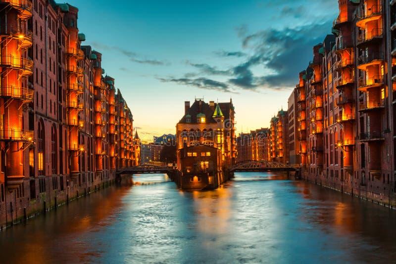 Het Pakhuisdistrict Speicherstadt tijdens schemeringzonsondergang in Hamburg, Duitsland Verlichte pakhuizen in Hafencity-kwart bi royalty-vrije stock afbeelding