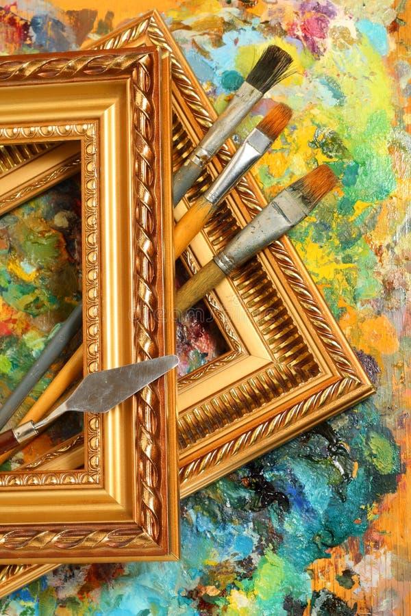 Het palet, de penselen en de frames van de kunstenaar stock fotografie