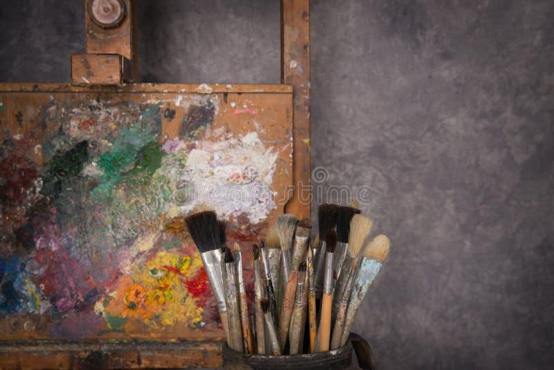 Het palet van de kunstenaar, borstels, schildersezel stock fotografie