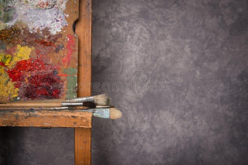 Het palet van de kunstenaar, borstels, schildersezel royalty-vrije stock afbeelding