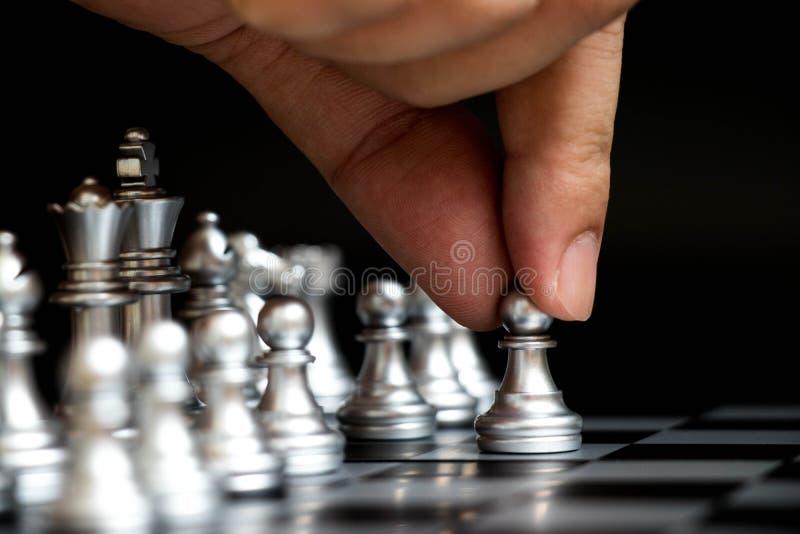 Het pand van de bedrijfsmensengreep aan eerste beweging in schaakspel stock foto