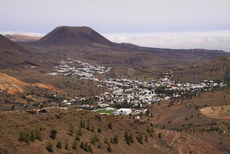Het panorama op wit dorp in vallei met kegel van vulkaanachtergrond en het diepe hangen betrekt in horizon - Haria, Lanzarote royalty-vrije stock afbeelding