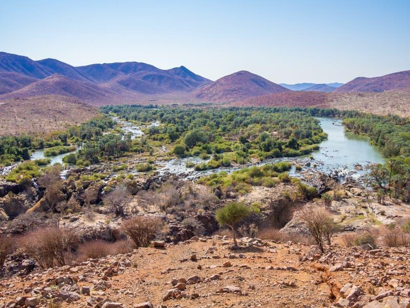 Het panorama over de Rivier en Epupa van Kunene valt bij grens tussen Namibië en Angola, Afrika stock foto's