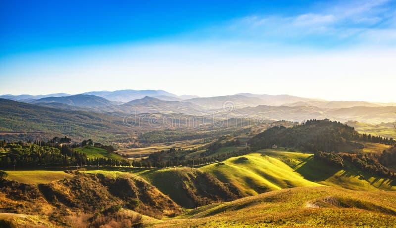 Het panorama van de Volterrawinter, rollende heuvels en groene gebieden op zonnen stock afbeeldingen