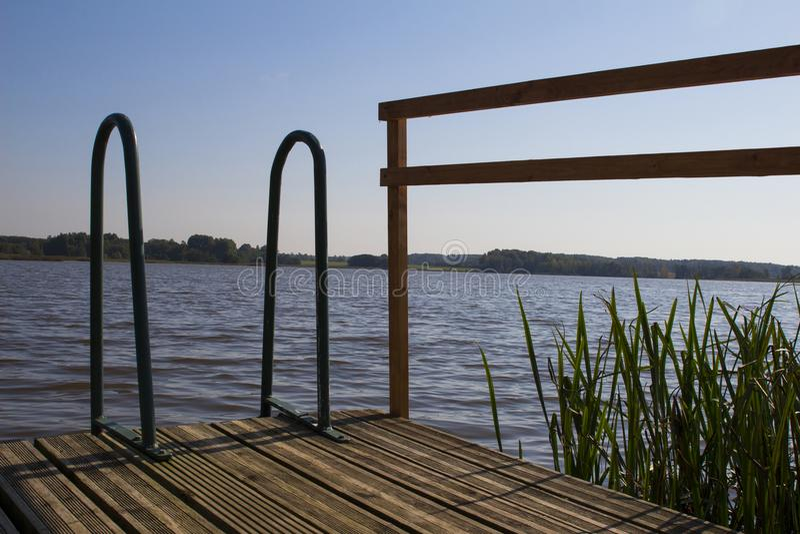 Het panorama van de de zomeravond van meer met traliewerk voor zwemmers, Lat stock afbeelding