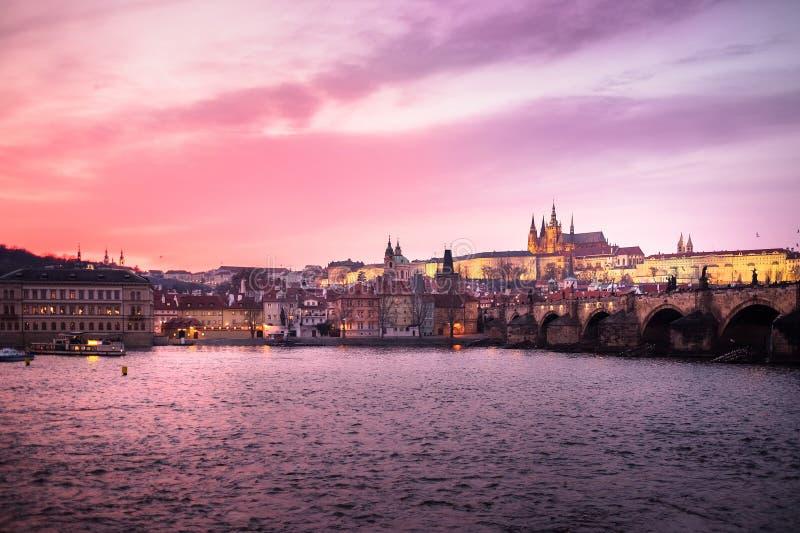 Het panorama van het Kasteel van Praag, Charles Bridge en St Vitus Cathedral dacht in de Vltava-rivier na bij schemer stock afbeeldingen