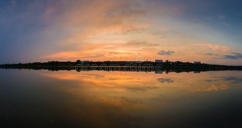 Het panorama van kleurrijke zonsondergang betrekt symmetrisch overdacht de meeroppervlakte Idyllische de zomeravond, natuurlijke  stock afbeelding