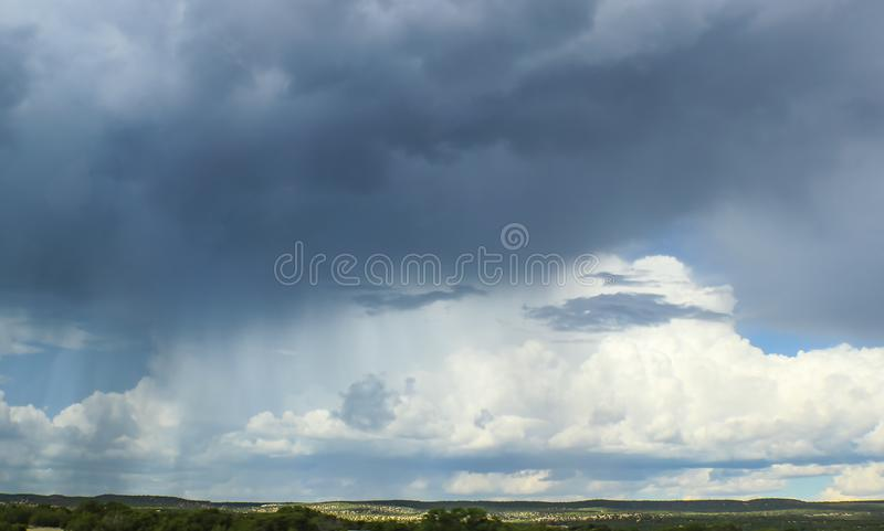 Het panorama van New Mexico Cloudscape met regen die op een deel van horizon en zon het breken door zware wolken op een ander dee royalty-vrije stock afbeeldingen