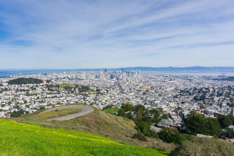 Het panorama van San Francisco naar het financiële district en de stad in; wildflowers en windende weg in de voorgrond, royalty-vrije stock afbeelding