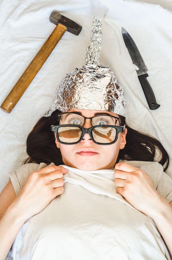 Het paranoïde meisje draagt foliehoed en slaap met wapen en verschillende glazen wegens geestelijke wanorde stock afbeelding